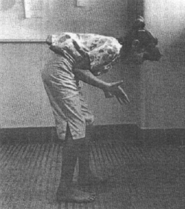 A young girl stands on the electric floor and is shocked mid-stim